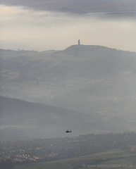 Military power over 2 millennium, an Apache attack helicopter flies over  Castle Hill Iron Age hill fort , Huddersfield